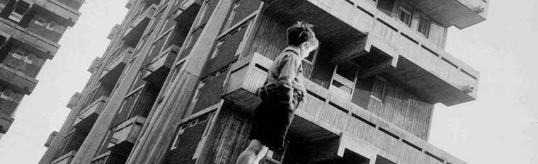View from ground level of hanging balconies in Area C with child in foreground, 1965. SC438977