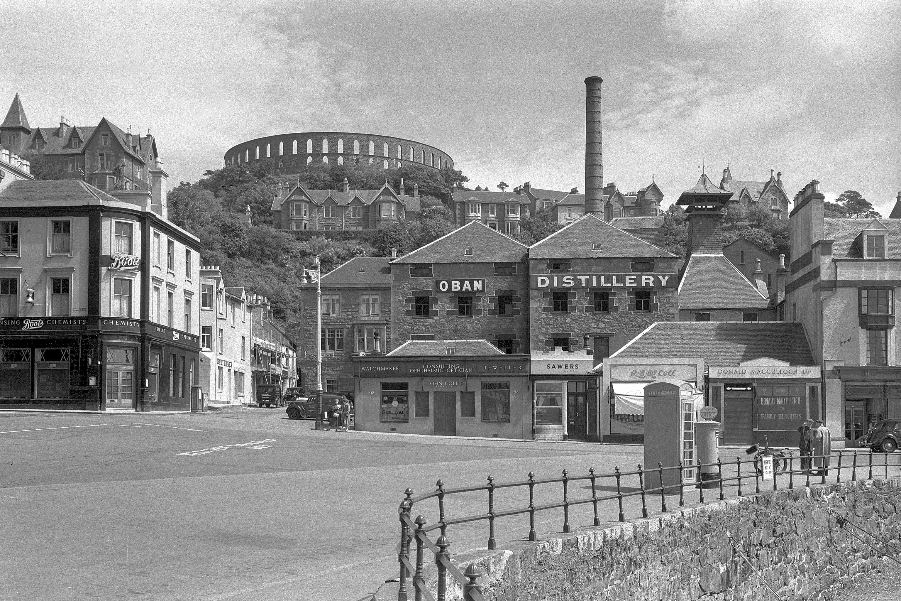 "A black and white photograph of a building with the words ""Oban Distillery"" on it. There is a large chimney on the building and a circular folly with arches."