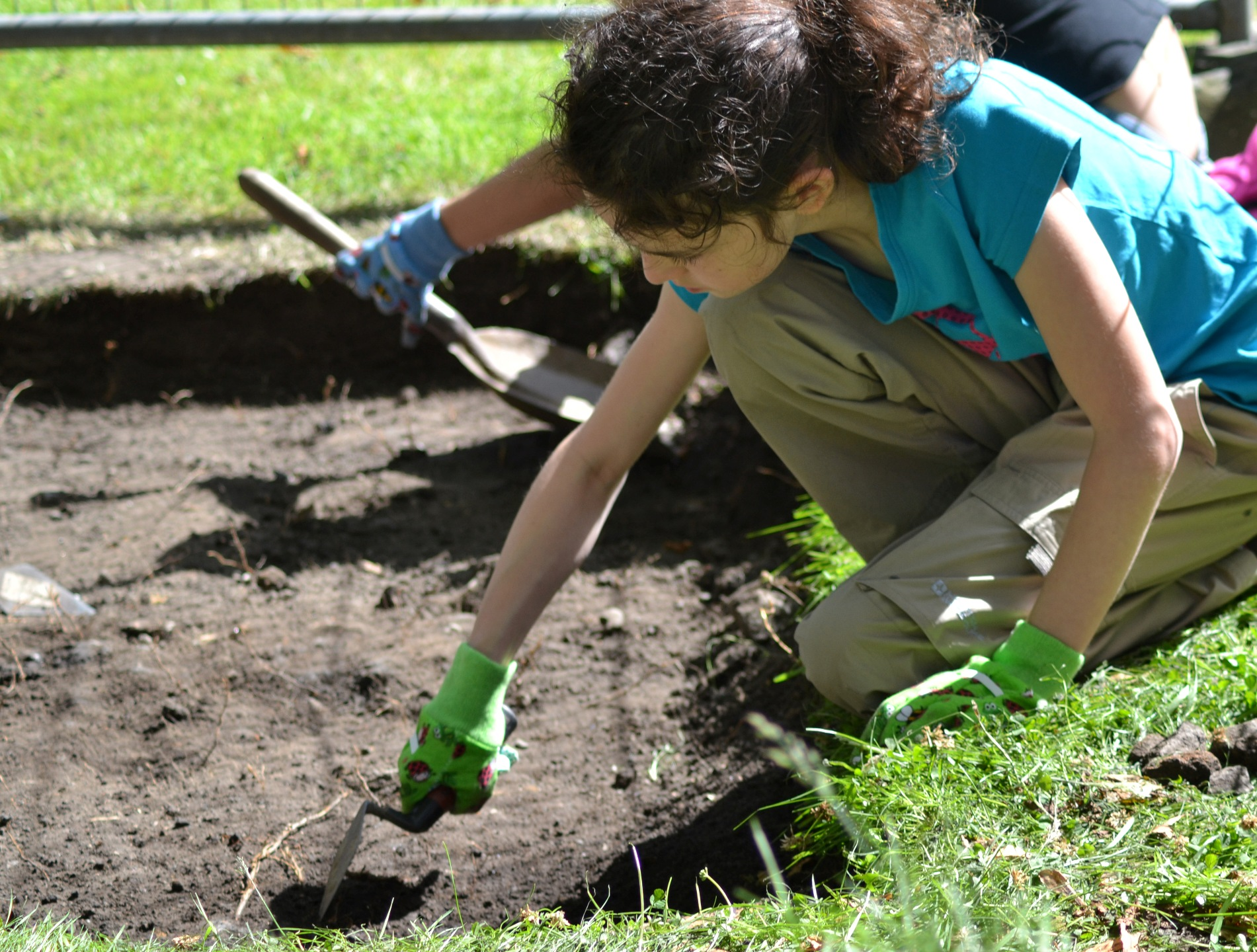 A photograph of a young girl with green gloves digging in a shallow trench with a trowel