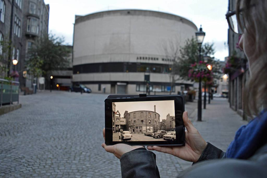 A photograph of a woman standing in front of a building in Aberdeen, holding a tablet with an archival image of the same building on it.